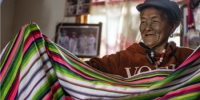 独龙族妇女李文仕在家里展示她亲手织的独龙毯。新华社记者 江文耀 摄 - 云南频道